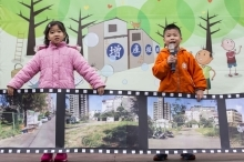 two kids holding mic and billboard